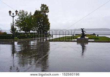 View on the Volga quay of the Samara city in heavy rain. City embankment at rainy autumn day