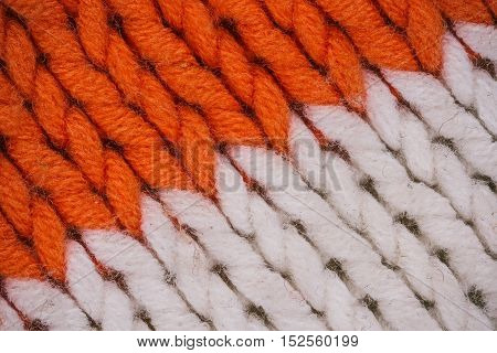 Macro flat view of knitted surface in orange and white