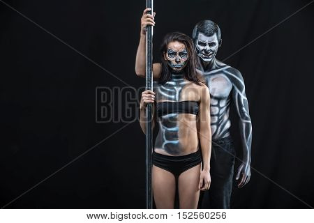 Grinning couple of pole dancers with horrific body-art stands next to a pylon on a dark background in the studio. They dressed in black sportswear and hold the right hands on the pylon. Horizontal.
