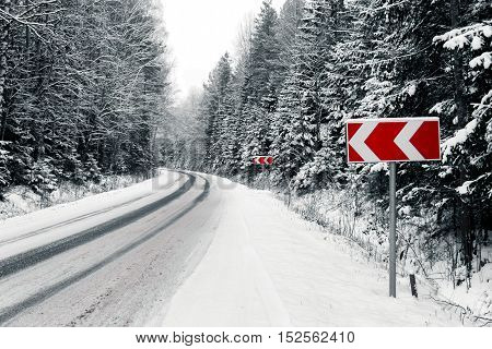 Forest road with snow and warning signs