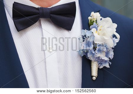 Blue and white boutonniere of hydrangea and freesia flowers