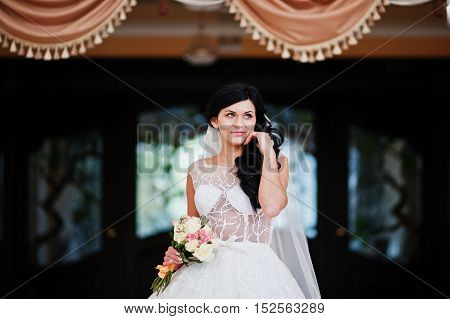 Temptation Model Brunette Bride At Exciting Wedding Dress With Bouquet At Hands With Tattoo Infinity
