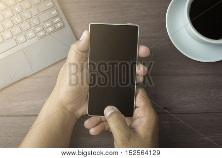 Adult hand holding and touch blank screen smartphone with coffee cup on wooden top table background lifestyle and relaxing conceptView from above