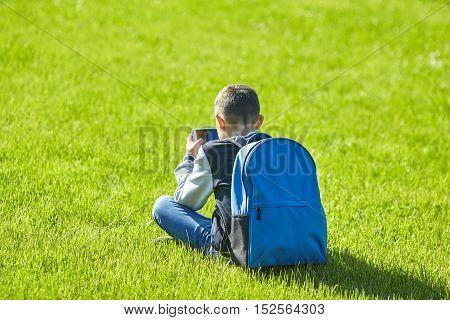 schoolboy using smartphone on a green lawn school playground