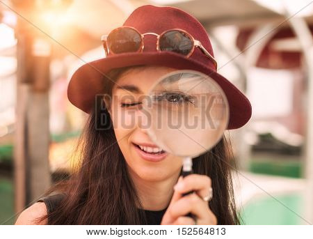 Funny young woman looking through a magnifying glass