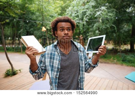 Confused african young man holding book and tablet outdoors