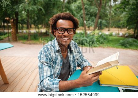 Cheerful african young man sitting and reading book outdoors