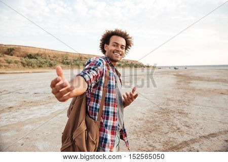 Happy african american young man with backpack inviting you to go with him