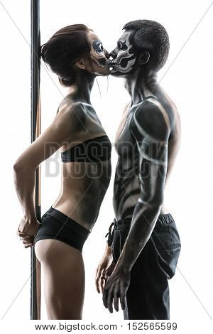 Kissing couple of pole dancers with horrific body-art stand in the studio on the white background. Girl holds a pylon with her hands from the back. They dressed in black sportswear. Vertical.