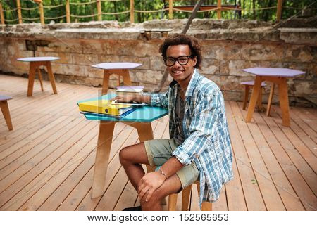 Cheerful young african man in glasses and plaid shirt sitting in outdoor cafe