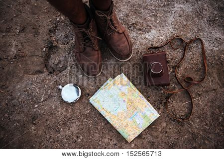 Top view of man standing on the ground near map, hip flask and leather vintage photo camera in case