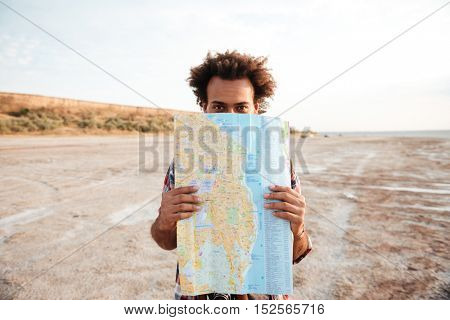 Playful african young man standing and hiding behind map outdoors