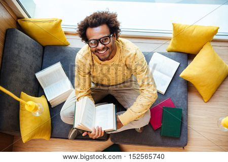 Top view of smiling african american young man with books studying at home