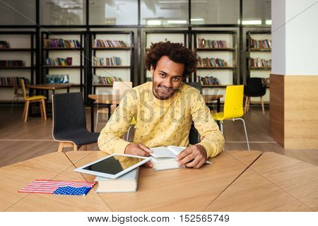Cheerful african american young man with tablet reading book in library