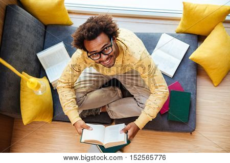Top view of cheerful african young man in glasses sitting and reading at home