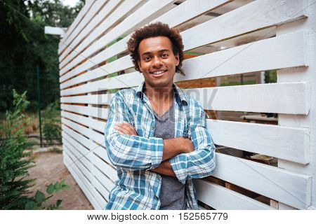 Smiling attractive african young man in plaid shirt standing outdoors with arms crossed