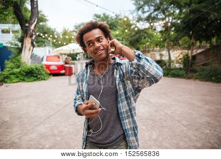 Smiling cute african young man in earphones listening to music from cell phone