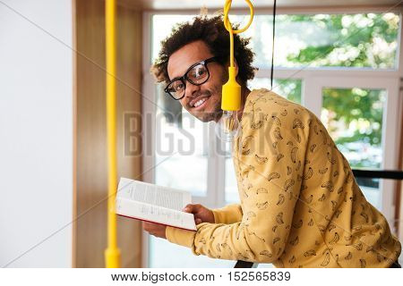 Happy handsome african young man in glasses reading a book at home