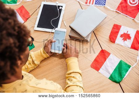 Closeup of man using mobile phone and tablet at the table with flags of countries