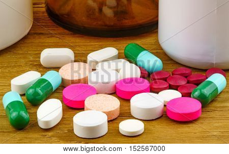 Colorful pills and capsule on a wooden table