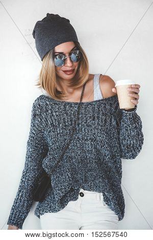Trendy hipster girl photo in fashion urban outfit. Grey oversize sweater, hat and sunglasses. Swag street style. Drinking coffee in take away paper cup. Instagram photo.