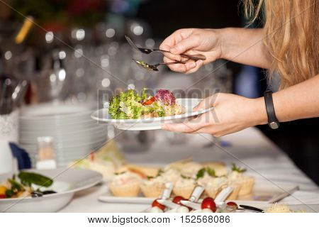 Woman hands put food on the plate from salad bar. Breakfast smorgasbord in the hotel