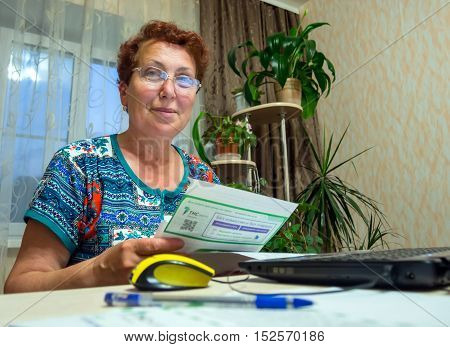 Voronezh Russia - June 19 2016: Elderly woman holding a receipt and is going to pay for it in the online bank