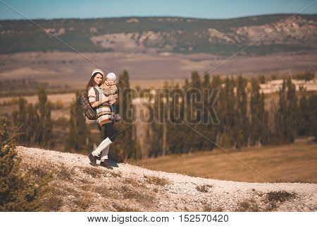Family on autumn hike. Young mom with kid hiking next to a mountain.