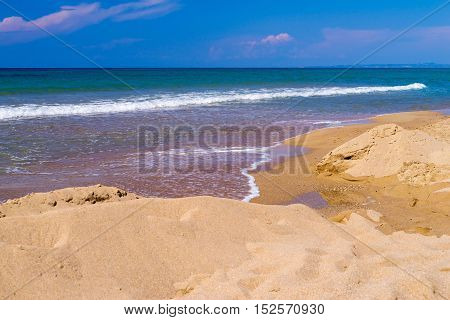 sea surf or inflow of water on the sandy coast and the sky on the horizon