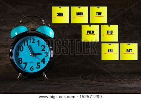 Day of week yellow sticky note with blue push pin and clock over wooden background