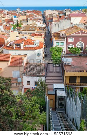 View from Parc del Castell (Malgrat de Mar, Spain) on funicular, roofs of the town, side-street leading to the sea and the sea on the horizon. Malgrat de Mar, Spain - May 03 2016.