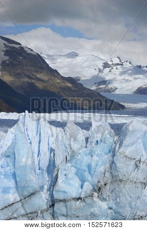 Hostile glacier peaks from Perito Moreno in front of mountain chain