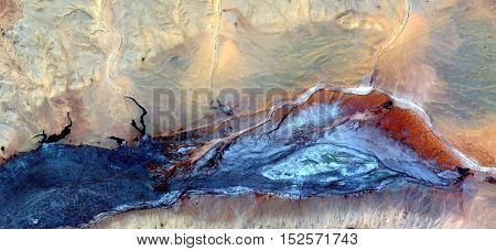 Abstract photography of landscapes of deserts of Africa from the air, blue river and red desert