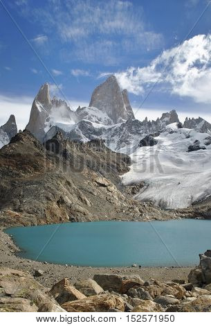 Two hikers feeling small standing in front of the massive Fitz Roy mountain with it's a beautiful emerald colored lake.