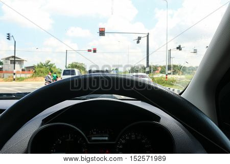 Driver stop car at red traffic light, image of inside car