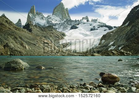 Fitz roy peaks with clear blue glacial lake shot from low perspective
