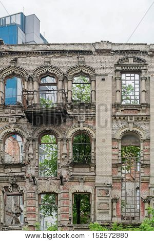 Abandoned damaged old house with blank windows against blue cloudy sky