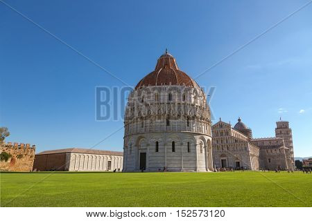 PISA, ITALY - SEPTEMBER 2016: Pisa Baptistery of St.John, Battistero di San Giovanni, Roman Catholic ecclesiastical building with Pisa leaning tower in background in Pisa, Italy on September 22, 2016