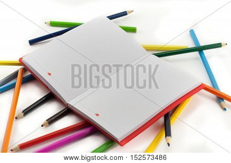 Colorful pencils and notebook isolated on white