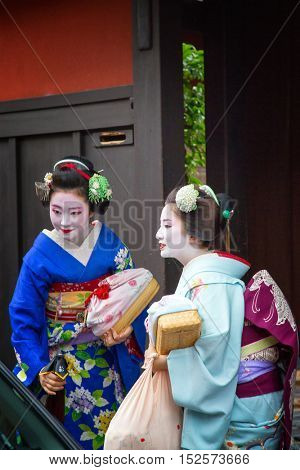 KYOTO, JAPAN - 15th June 2016. Geisha emerge from a taxi at a house in Gion, Kyoto, Japan.