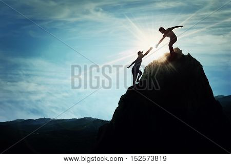 Silhouette of helping hand between two boys climbing a rocky dangerous cliff. Friendly hand on the high mountain hike. Inspirational teamwork faith and support symbol.