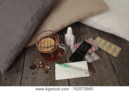 pills, thermometer, medical tea with lemon. a cold or sickness in the winter or fall.