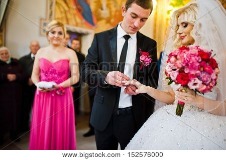 Groom wears a wedding ring on the hand of the bride
