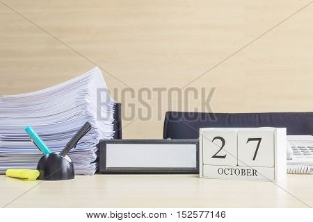 Closeup white wooden calendar with black 27 october word on blurred brown wood desk and wood wall textured background in office room view with copy space selective focus at the calendar