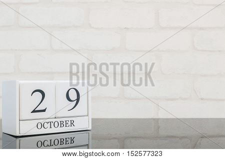 Closeup white wooden calendar with black 29 october word on black glass table and white brick wall textured background with copy space selective focus at the calendar