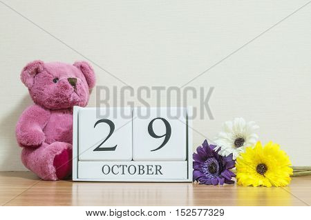 Closeup surface white wooden calendar with black 29 october word on brown wood desk and cream color wallpaper in room textured background with copy space selective focus at the calendar