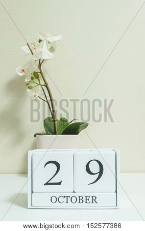 Closeup white wooden calendar with black 29 october word with white orchid flower on white wood desk and cream color wallpaper in room textured background selective focus at the calendar