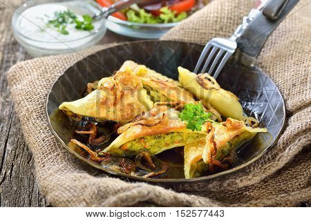 Fried Swabian ravioli, so-called Maultaschen, with vegetable filling served with side salad and creamy herb cheese