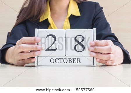 Closeup white wooden calendar with black 28 october word in blurred working woman hand on wood desk in office room selective focus at the calendar