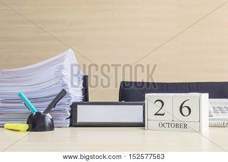 Closeup white wooden calendar with black 26 october word on blurred brown wood desk and wood wall textured background in office room view with copy space selective focus at the calendar